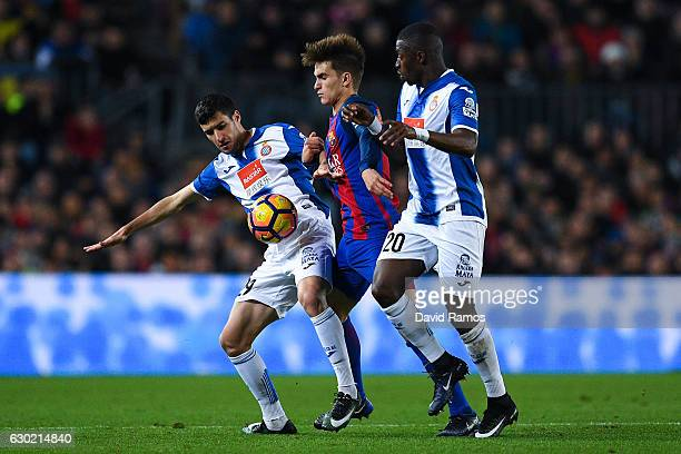 Denis Suarez of FC Barcelona competes for the ball with Aaron Martin and Pape Diop of RCD Espanyol during the La Liga match between FC Barcelona and...