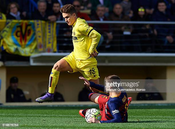 Denis Suarez of Villarreal is tackled by Gerard Pique of Barcelona during the La Liga match between Villarreal CF and FC Barcelona at El Madrigal on...