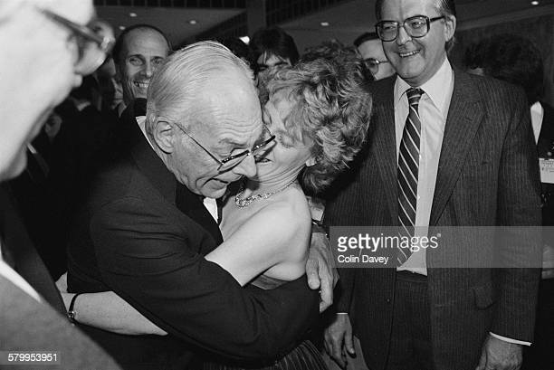 Denis Thatcher husband of British Prime Minister Margaret Thatcher embracing a woman UK 10th October 1984 He is being watched by Conservative...