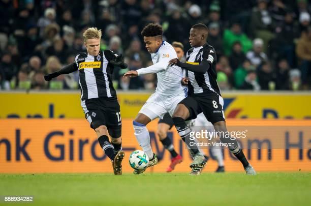 Denis Zakaria and Oscar Wendt of Borussia Moenchengladbach and Weston McKennie of FC Schalke 04 during the Bundesliga match between Borussia...