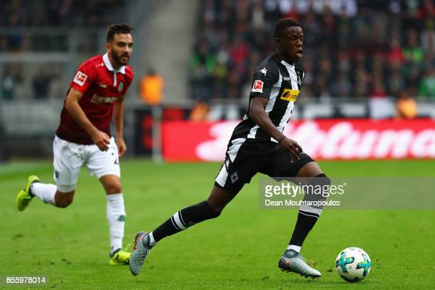 Denis Zakaria Borussia Monchengladbach gets past the tackle from Kenan Karaman of Hannover 96 during the Bundesliga match between Borussia...