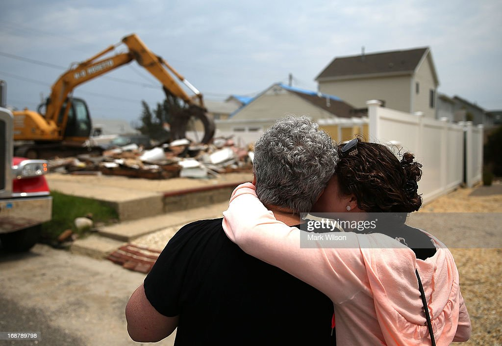 Denise Avrutik (L), gets a hug from her daughter Julianne Avrutik as they watch their home get demolished after it was damaged six months ago by Superstorm Sandy, May 15, 2013 in Ortley Beach, New Jersey. Mrs. Avrutik's family has owned the home since 1959 when she was only three years old. The neighboring town of Mantoloking had all 528 homes either damaged or destroyed by the storm and say that at least 50 homes are scheduled to be demolished in the up coming weeks.