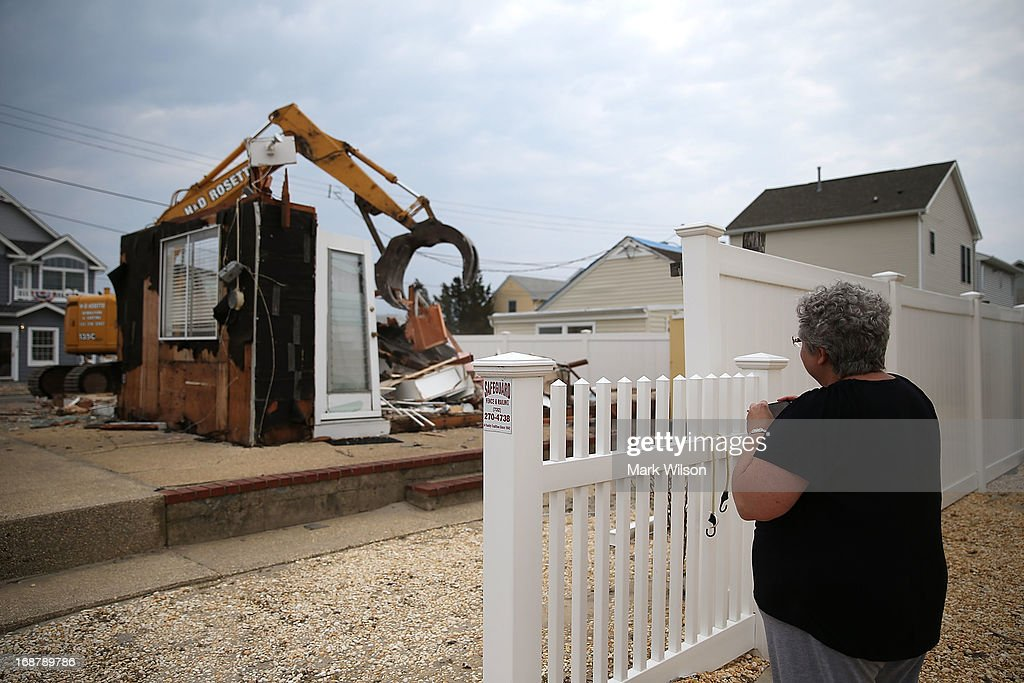 Denise Avrutik watches as the home she grew up in is demolished after it was damaged six months ago by Superstorm Sandy, May 15, 2013 in Ortley Beach, New Jersey. Mrs. Avrutik's family has owned the home since 1959 when she was only three years old. The nearby town of Mantoloking had all 528 homes either damaged or destroyed by the storm and say that at least 50 homes are scheduled to be demolished in the upcoming weeks.