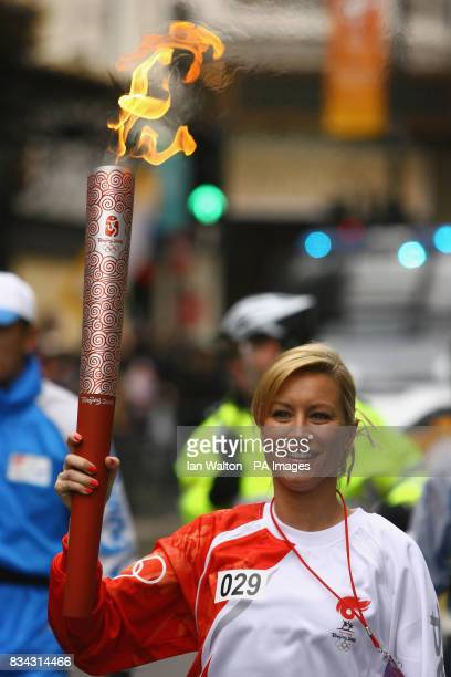 Denise Van Outen carries the Olympic torch during its relay journey across London on its way to the lighting of the Olympic cauldron at the O2 Arena...