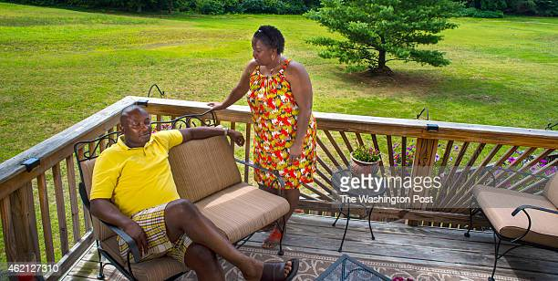 Denise Watson and her husband Samuel Kargbo on their back deck which has a view of the 11th fairway of the neighborhood golf course behind their town...