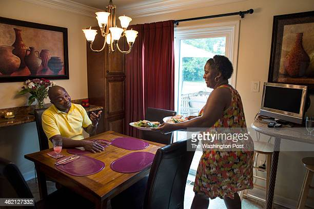 Denise Watson brings lunch to the table in the dinning area of the kitchen as her husband Samuel Kargbo waits on August 2 2014 in Upper Marlboro MD...