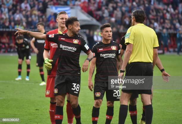 Deniz Aytekin speak with Bernd Leno Karim BellarabiCharles Aranguiz of Leverkusen during the Bundesliga match between Bayer 04 Leverkusen and VfL...