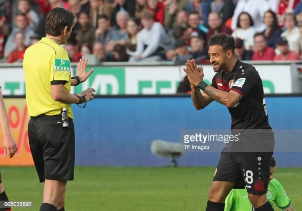 Deniz Aytekin speak with Karim Bellarabi of Leverkusen during the Bundesliga match between Bayer 04 Leverkusen and VfL Wolfsburg at BayArena on April...