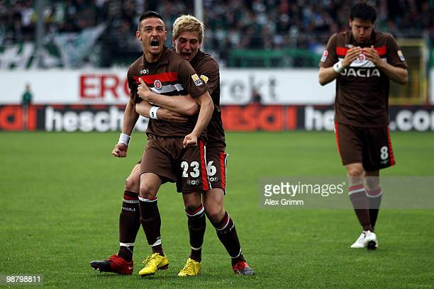 Deniz Naki of St Pauli celebrates his team's first goal with team mates Bastian Oczipka and Florian Bruns of St Pauli during the Second Bundesliga...