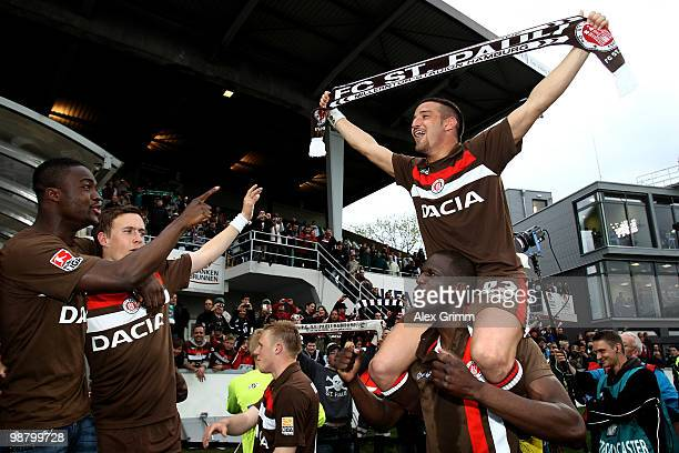 Deniz Naki of St Pauli sits on the shoulders of team mate Morike Sako as he celebrates with team mates after the Second Bundesliga match between...