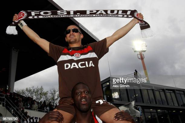 Deniz Naki of St Pauli sits on the shoulders of team mate Morike Sako as they celebrate after the Second Bundesliga match between SpVgg Greuther...