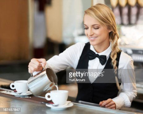 Denmark, Aarhus, Female barista pouring milk into coffee cup : Stock Photo