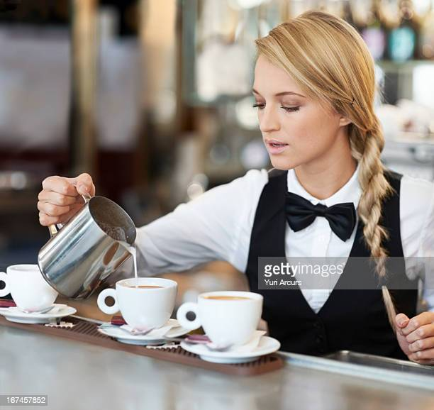 Denmark, Aarhus, Female barista pouring milk into coffee cup