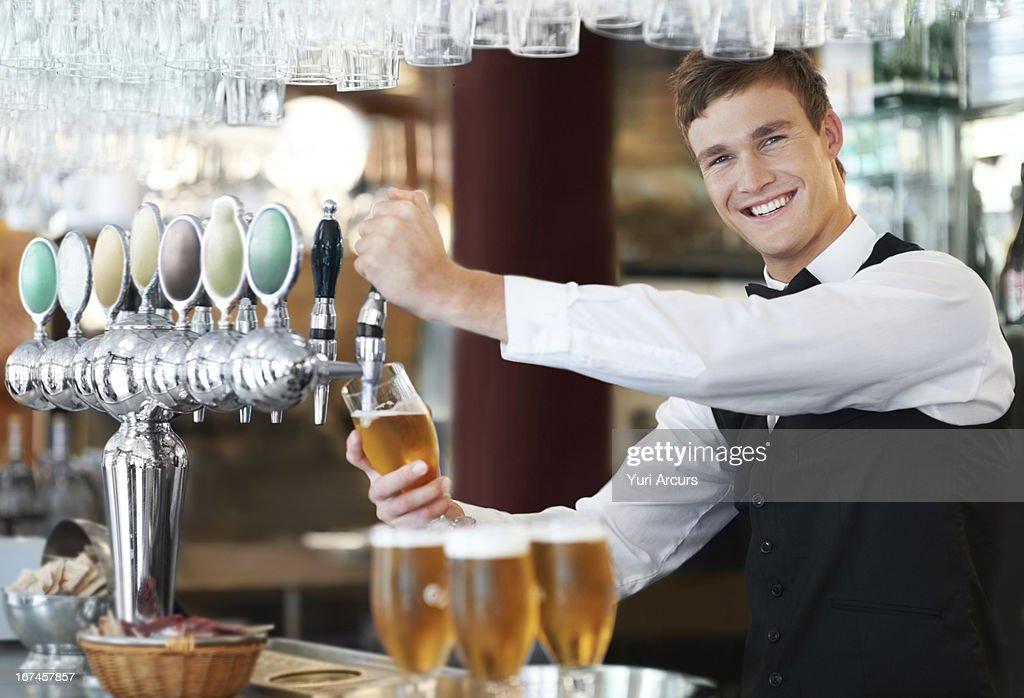 Denmark, Aarhus, Portrait of bartender pouring beer : Stock Photo