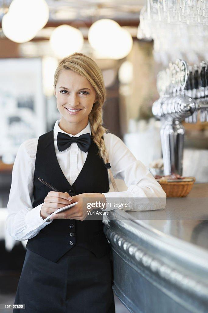 Denmark, Aarhus, Portrait of smiling waitress standing by bar counter