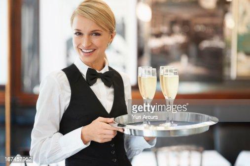 Denmark, Aarhus, Portrait of waitress holding champagne flutes on tray : Stock Photo