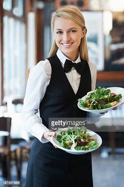 Denmark, Aarhus, Portrait of young waitress holding plates with salad