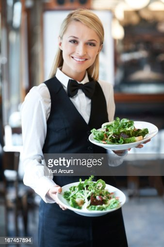 Denmark, Aarhus, Portrait of young waitress holding plates with salad : Stock Photo