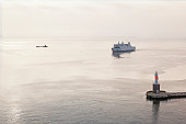 Denmark, Aarhus, View of arriving ferryboat at harbour entrance with lighthouse at dusk