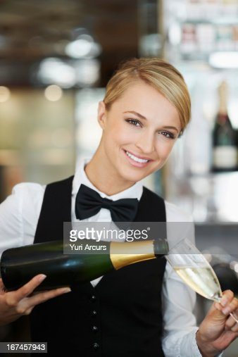 Denmark, Aarhus, Waitress pouring champagne into champagne flute : Stock Photo