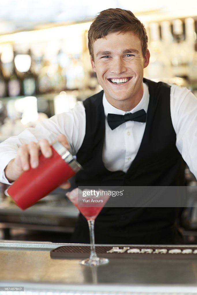 Denmark, Aarhus, Young bartender pouring cocktail  : Stock Photo