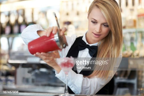 Denmark, Aarhus, Young female bartender pouring cocktail  : Stock Photo