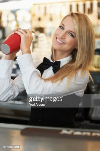 Denmark, Aarhus, Young female bartender using cocktail shaker : Stock Photo