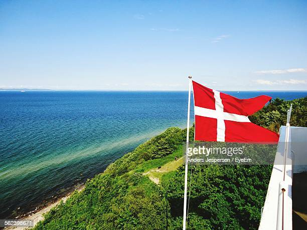 Denmark Flag Against Calm Blue Sea And Clear Sky