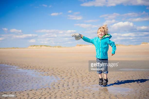 Denmark, Romo, Boy jumping at North Sea, smiling