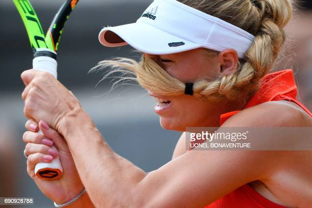 Denmark's Caroline Wozniacki has her hair in the eyes as she returns the ball to Canada's Francoise Abanda during their tennis match at the Roland...