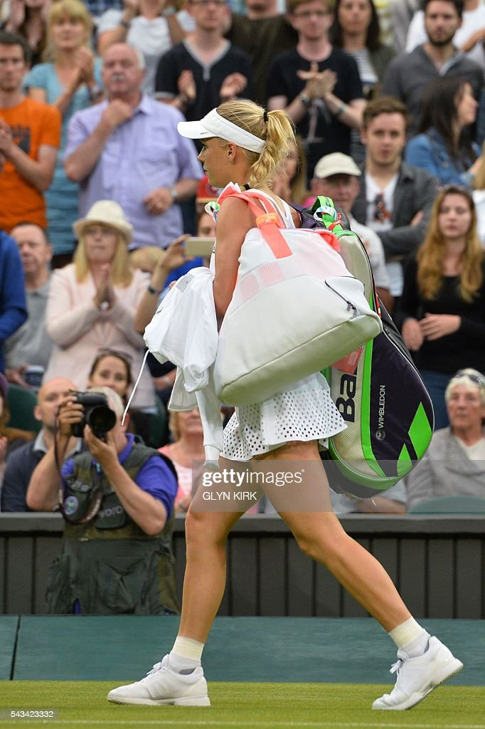 Denmark's Caroline Wozniacki leaves the court after Russia's Svetlana Kuznetsova won their women's singles first round match on the second day of the 2016 Wimbledon Championships at The All England Lawn Tennis Club in Wimbledon, southwest London, on June 28, 2016. / AFP / GLYN