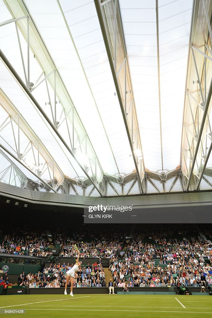 Denmark's Caroline Wozniacki serves against Russia's Svetlana Kuznetsova under the roof on Centre Court during their women's singles first round match on the second day of the 2016 Wimbledon Championships at The All England Lawn Tennis Club in Wimbledon, southwest London, on June 28, 2016. / AFP / GLYN