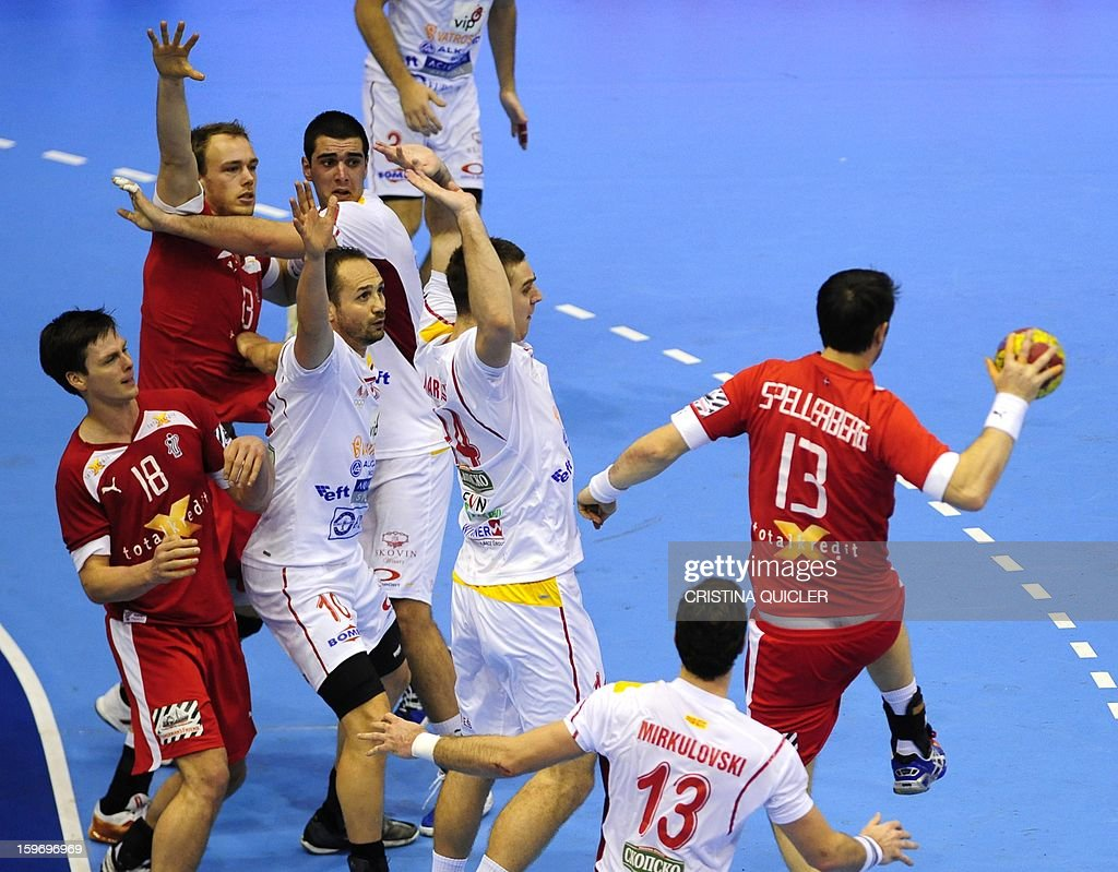 Denmark's centre back Bo Spellerberg (R) jumps with the ball during the 23rd Men's Handball World Championships preliminary round Group B match Denmark vs Macedonia at the Palacio de Deportes San Pablo in Sevilla on January 18, 2013.AFP PHOTO/ CRISTINA QUICLER