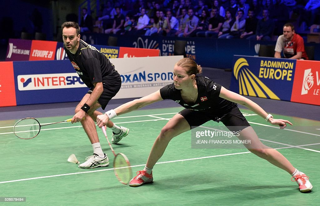 Denmark's Christina Pedersen (front), flanked by Denmark's Joachim Nielsen (rear), hits a shot against Dutch players Jacco Arends and Selena Piek during the 2016 European Badminton Championships mix double semi-final match between Denmark and Netherlands, on April 30, 2016 in Mouilleron-le-Captif, western France. / AFP / JEAN