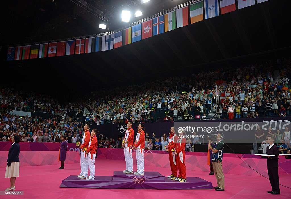 Denmark's Christinna Pedersen and Joachim Fischer, (Centre R) China's Zhang Nan and Zhao Yunlei, (C) and compatriots Xu Chen and Ma Jin (Centre L) listen to a national anthem after they were awarded bronze, gold and silver medals respectively following the Mixed Doubles medal matches at the London 2012 Olympic Games in London, on August 3, 2012.