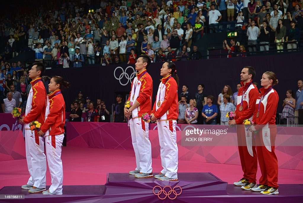 Denmark's Christinna Pedersen and Joachim Fischer, (R) China's Zhang Nan and Zhao Yunlei, (C) and compatriots Xu Chen and Ma Jin (L) listen to a national anthem after they were awarded bronze, gold and silver medals respectively following the Mixed Doubles medal matches at the London 2012 Olympic Games in London, on August 3, 2012.