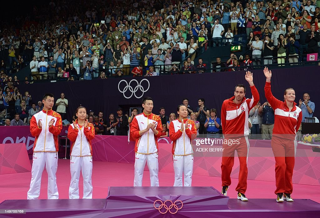 Denmark's Christinna Pedersen (R) and Joachim Fischer (2nd R) step forward to receive their bronze medals as China's Zhang Nan, (3rd L) Zhao Yunlei, (3rd R) and compatriots Xu Chen (L) and Ma Jin (2nd L) look on following the Mixed Doubles medal matches at the London 2012 Olympic Games in London, on August 3, 2012. AFP PHOTO / ADEK BERRY