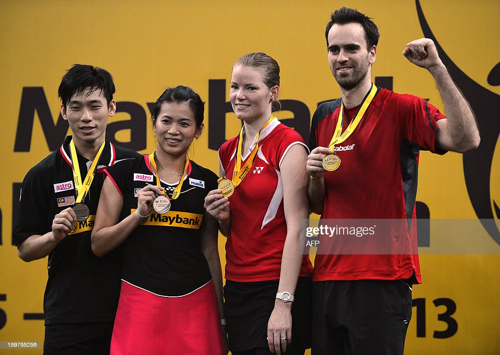 Denmark's Christinna Pedersen (2nd R) and partner Joachim Fischer Nielsen (R) celebrate winning the gold medal during awards ceremony after defeating Malaysia's Peg Soon Chan (L) and Liu Ying Goh (2nd L) in the mixed doubles final at the Malaysia Open Badminton Superseries in Kuala Lumpur on January 20, 2013.