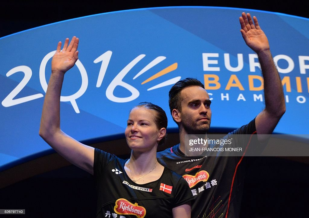 Denmark's Christinna Pedersen (L) and teammate Joachim Fischer Nielsen react on the podium after winning their 2016 European Championships Badminton mixed doubles final match in Mouilleron-le-Captif, western France, on May 1, 2016. / AFP / JEAN