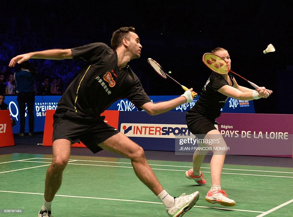 Denmark's Christinna Pedersen (R) flanked by teammate Joachim Fischer Nielsen returns the ball to Denmark's Niclas Nohr and teammate Sara Thygesen during their 2016 European Championships Badminton mixed doubles final match in Mouilleron-le-Captif, western France, on May 1, 2016. / AFP / JEAN