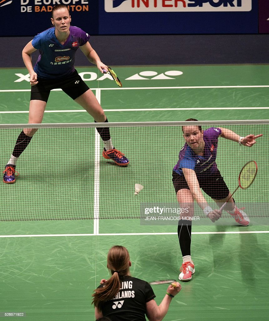 Denmark's Christinna Pedersen (front), flanked by teammate Kamilla Rytter Juhl, hits a return against Dutch players Samantha Barning and Iris Tabeling during the 2016 European Badminton Championships Women's double semi-final match between Denmark and Netherlands, on April 30, 2016 in Mouilleron-le-Captif, western France. / AFP / JEAN