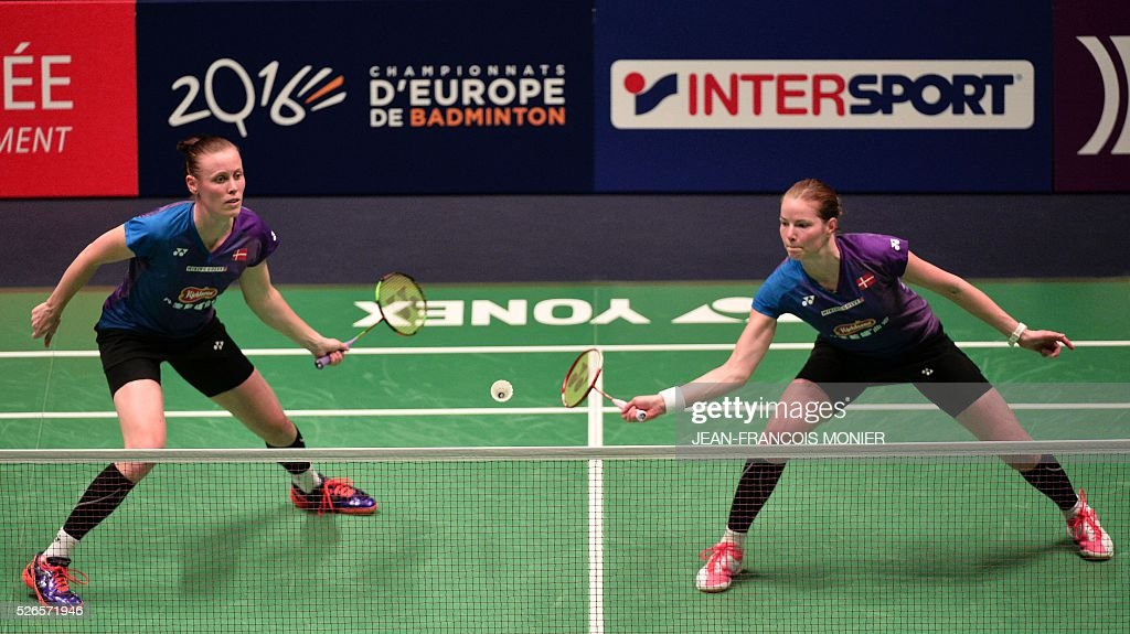 Denmark's Christinna Pedersen (front), flanked by teammate Kamilla Rytter Juhl, prepares to hit a return against Dutch players Samantha Barning and Iris Tabeling during the 2016 European Badminton Championships Women's double semi-final match between Denmark and Netherlands, on April 30, 2016 in Mouilleron-le-Captif, western France. / AFP / JEAN