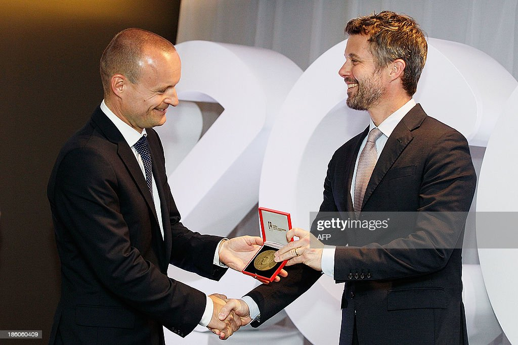 Denmark's Crown Prince Frederik (R) presents General Manager of ECCO Shoes, Morten Lauge with Prince Henrik's Medal of Honour at an offical ceremony of the Diploma of the Danish Export Association and His Royal Highness Prince Henrik's Medal of Honour to ECCO Shoes Pacific in Sydney on October 28, 2013. Prince Frederik and his whife Princess Mary are on a 5-day visit to Australia to celebrate the 40th anniversary of the Sydney Opera House. AFP PHOTO / POOL / Brendon Thorne