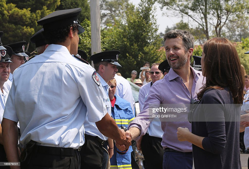 Denmark's Crown Princes Frederick (2nd R) and Princess Mary (R) meet volunteer firefighters at the Winmalee fire station, 85 kms west of Winmalee on October 27, 2013. Mary and her husband, Denmark's Crown Princes Frederick, visited the station to thank firefighters for their work during the bush fires that started October 18, destroying more than 200 properties. Frederick and Mary are in Australia and to take part in the 40th birthday celebrations of the Sydney Opera House. AFP PHOTO / POOL / Rob Griffith