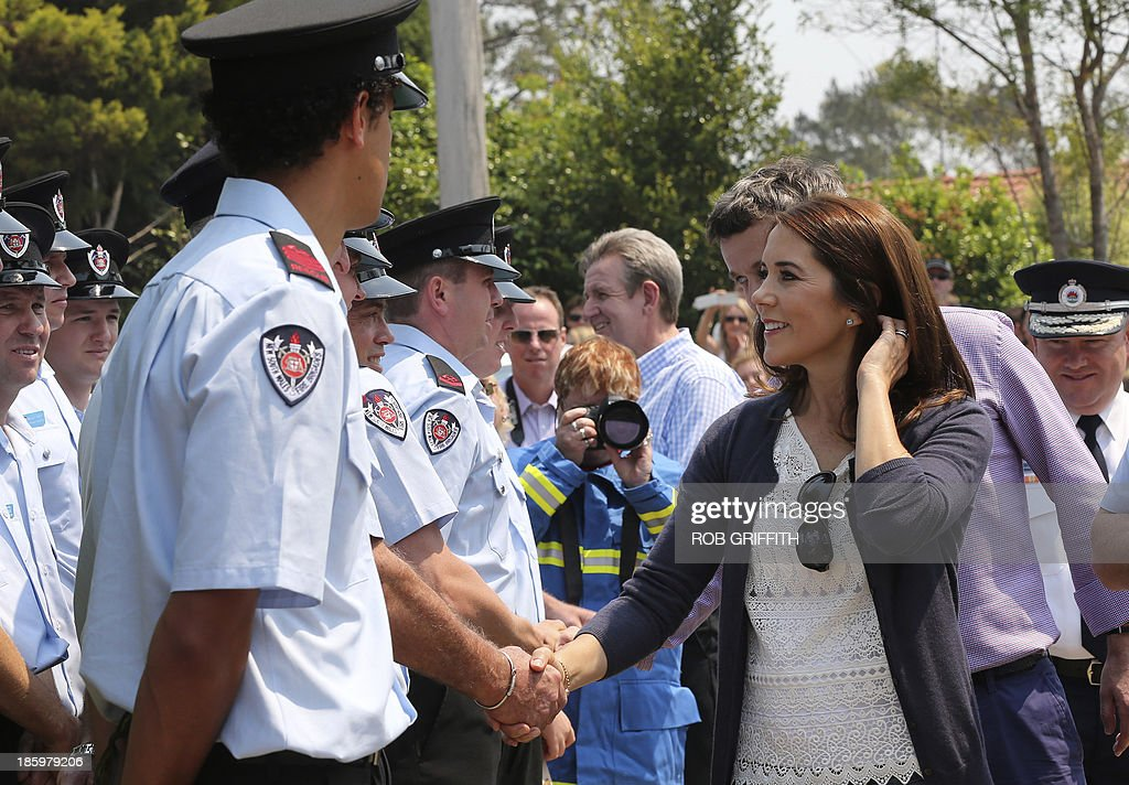 Denmark's Crown Princes Frederick (R-partly obscured) and Princess Mary (front R) meet volunteer firefighters at the Winmalee fire station, 85 kms west of Winmalee on October 27, 2013. Mary and her husband, Denmark's Crown Princes Frederick, visited the station to thank firefighters for their work during the bush fires that started October 18, destroying more than 200 properties. Frederick and Mary are in Australia and to take part in the 40th birthday celebrations of the Sydney Opera House. AFP PHOTO / POOL / Rob Griffith