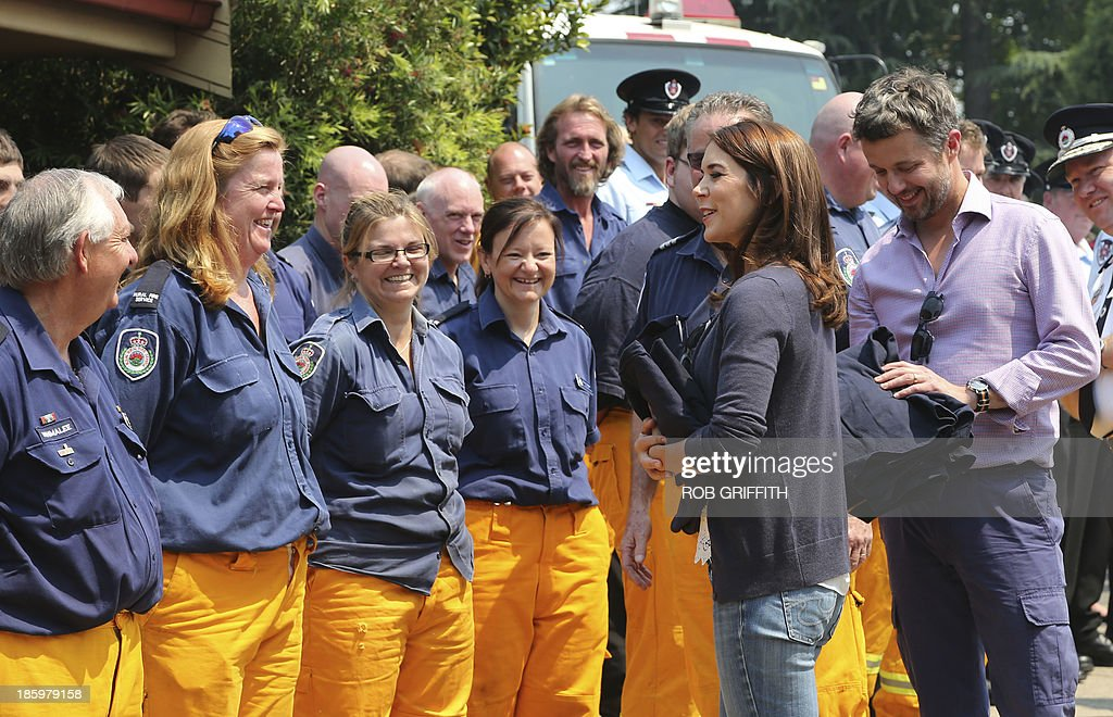 Denmark's Crown Princes Frederick (R) and Princess Mary (2nd R) receive gifts from volunteer firefighters at the Winmalee fire station, 85 kms west of Winmalee on October 27, 2013. The royal couple visited the station to thank firefighters for their work during the bush fires that started October 18, destroying more than 200 properties. Frederick and Mary are in Australia and to take part in the 40th birthday celebrations of the Sydney Opera House. AFP PHOTO / POOL / Rob Griffith