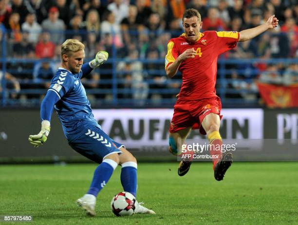 Denmark's goalkeeper Kasper Schmeichel kicks the ball in front of Montenegro's Luka Djordjevic during the FIFA WC 2018 Group E football qualification...