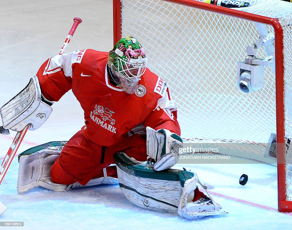 Denmark's goalkeeper Patrick Galbraith looks on the puck as it crosses the goal line from a shot by Sweden's Daniel Sedin (unseen) during the preliminary round match Denmark vs Sweden at the 2013 IIHF Ice Hockey World Championships on May 14, 2013 in Stockholm.