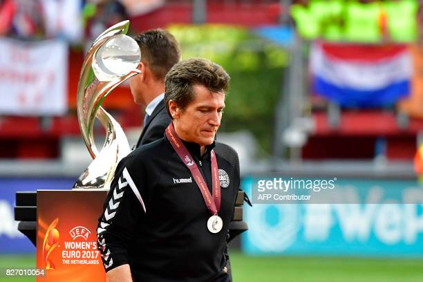 Denmark's head coach Nils Nielsen walks past the trophy as he reacts at the end of the UEFA Womens Euro 2017 football tournament final match between...