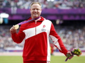 Denmark's Jackie Christiansen poses for photographs with the gold medal on the podium after winning the men's shot put F42/44 athletics event during...